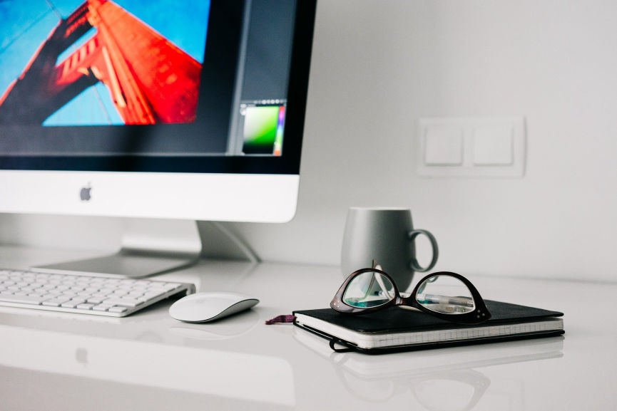 Desk with desktop turned on with a coffee mug, eye glasses and a book on the surface
